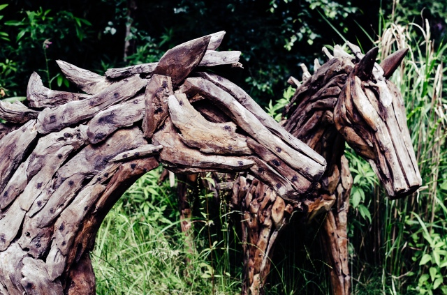 Two horses sculpted from multiple wooden segments on display at The Sculpture Park