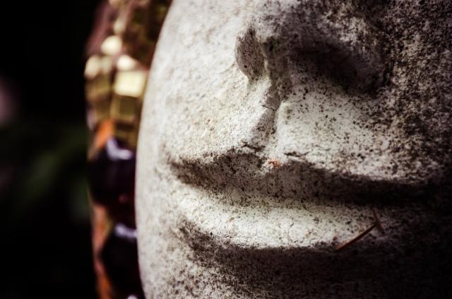 a facial close up of a smirking statue