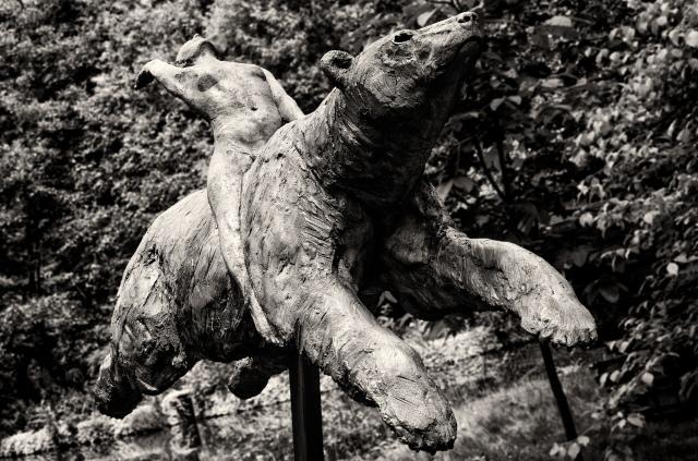 A sculpture of a naked women riding a bear